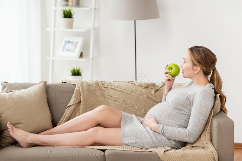 Happy pregnant woman eating green apple royalty free stock photo