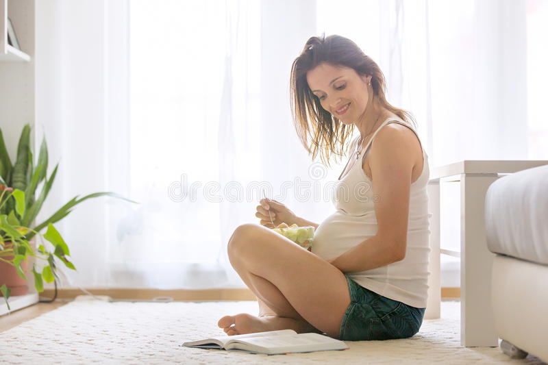 Happy pregnant woman eating salad at home stock image