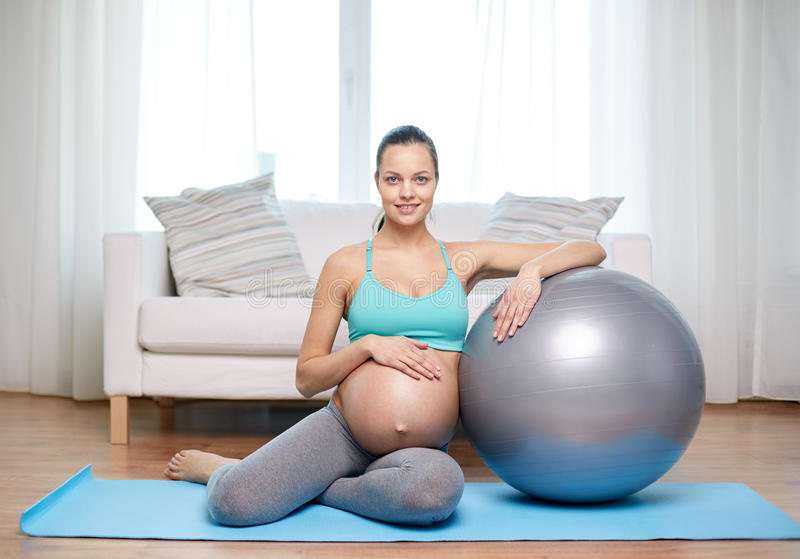 Happy pregnant woman with fitball at home royalty free stock image