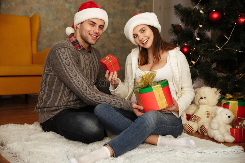 Happy pregnant woman with her husband wearing christmas hats royalty free stock photos