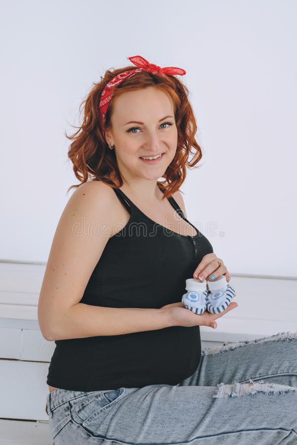 Happy pregnant woman holding booties, with a red bandage on his head. On a light background. Pregnancy red-haired young stock photos