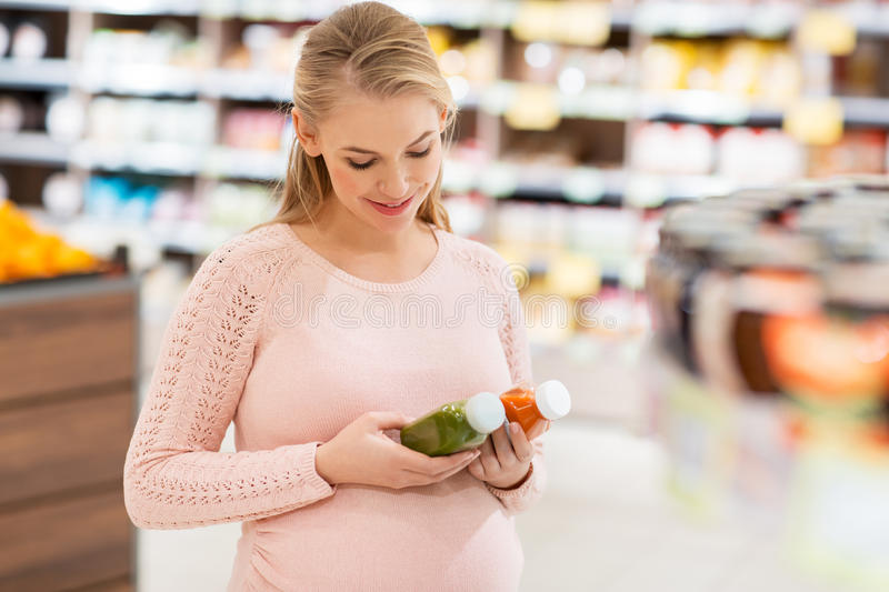 Happy pregnant woman with juice at grocery store royalty free stock images