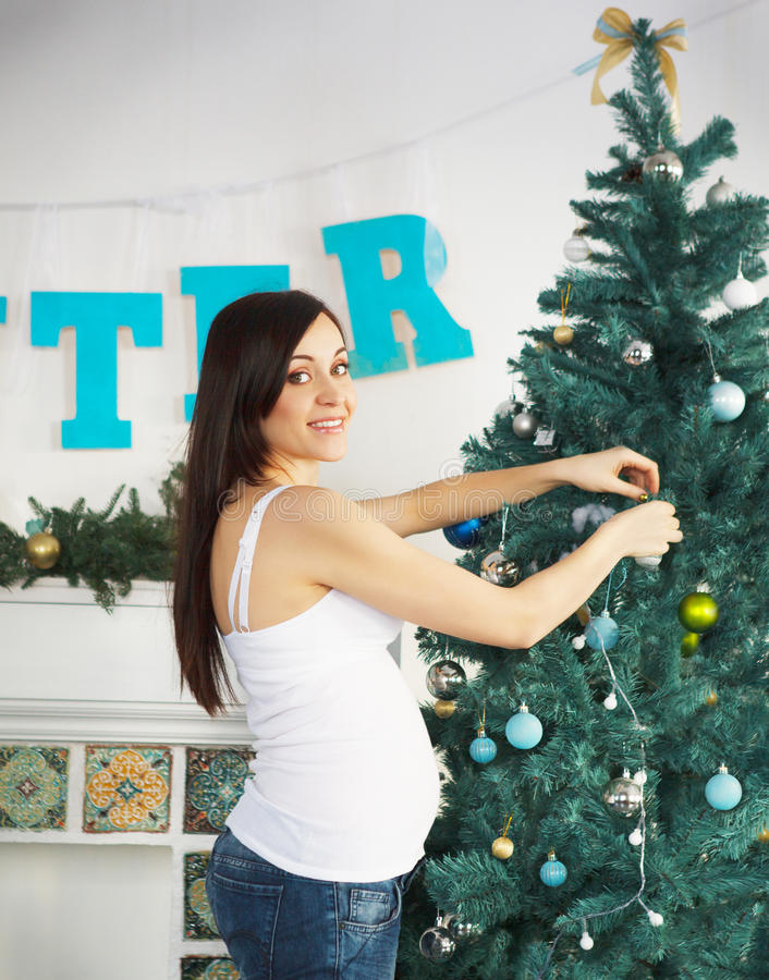 Happy pregnant woman near the Christmas tree stock images