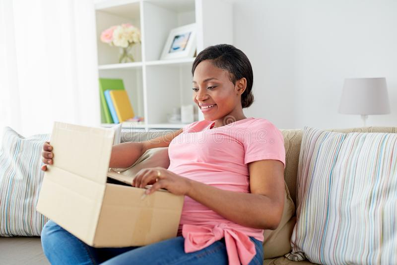 Happy pregnant woman opening parcel box at home stock photos