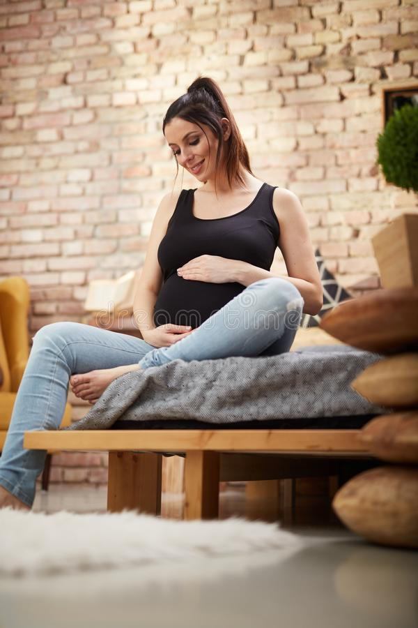 Happy pregnant woman sitting on bed at home stock photos