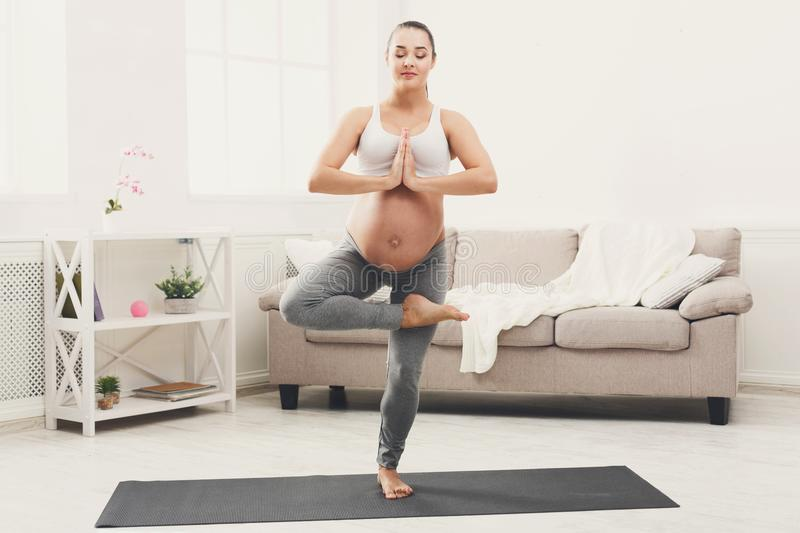 Happy pregnant woman training yoga in tree pose royalty free stock images