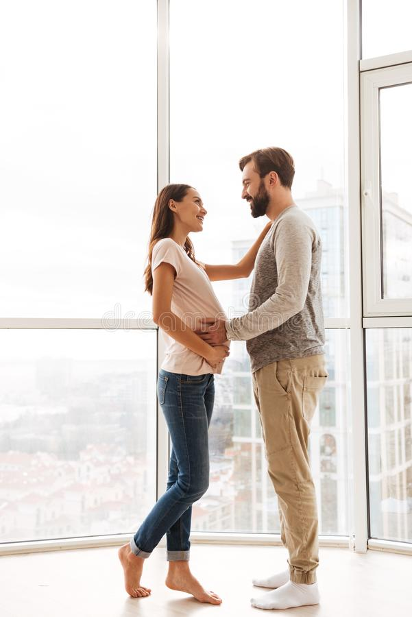 Happy pregnant young couple hugging. While standing together at a window stock image