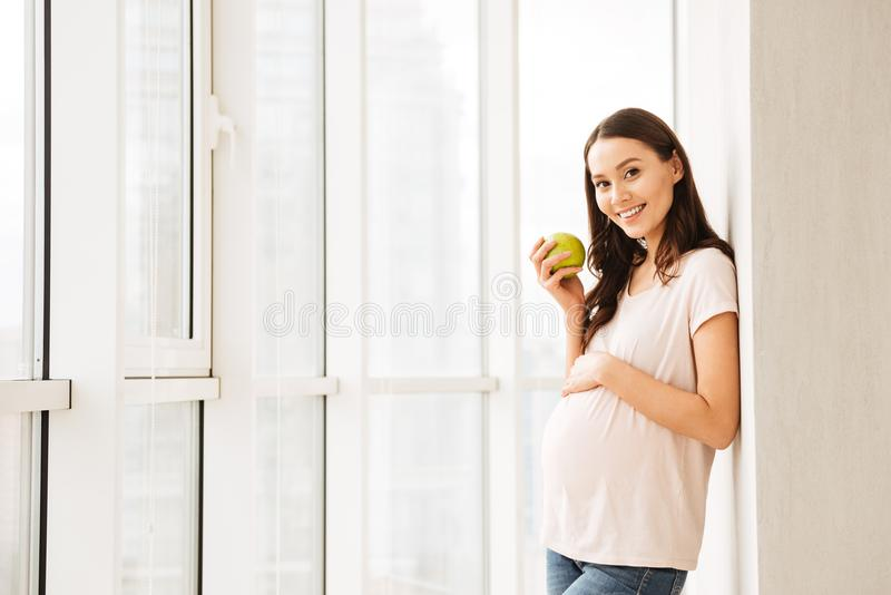 Happy pregnant young woman holding green apple. While standing at the window indoors royalty free stock photo