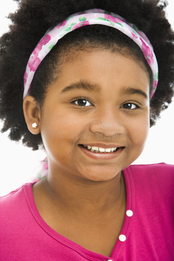 Happy preteen girl. African American girl wearing headband smiling at viewer royalty free stock photography