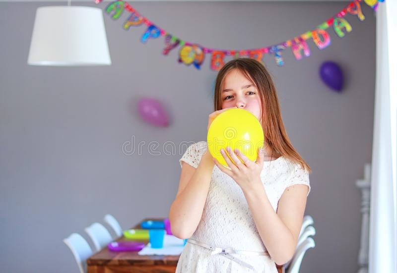 Happy preteen girl blowing yellow balloon decorating house preparing to kids birthday party with set up table royalty free stock photography