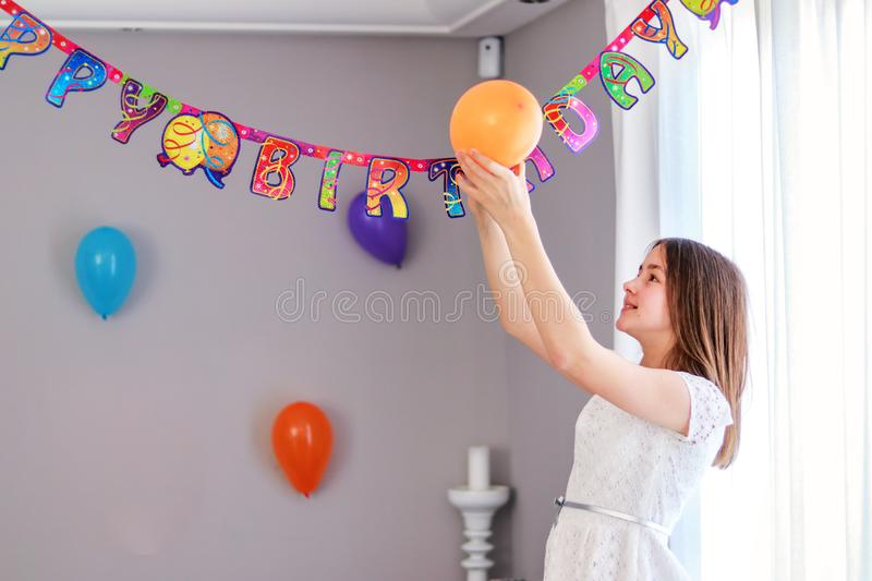 Happy preteen girl hanging up balloons decorating house preparing to birthday party. royalty free stock photography