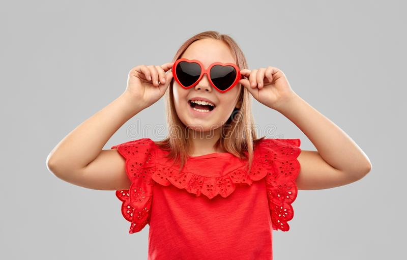 Happy preteen girl with heart shaped sunglasses stock photography
