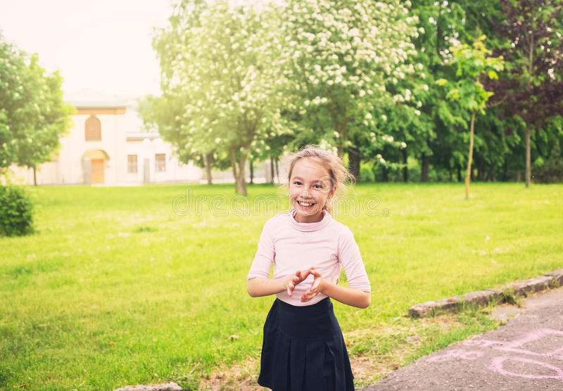 Happy preteen girl smiling on meadow in summer day at sunset stock images