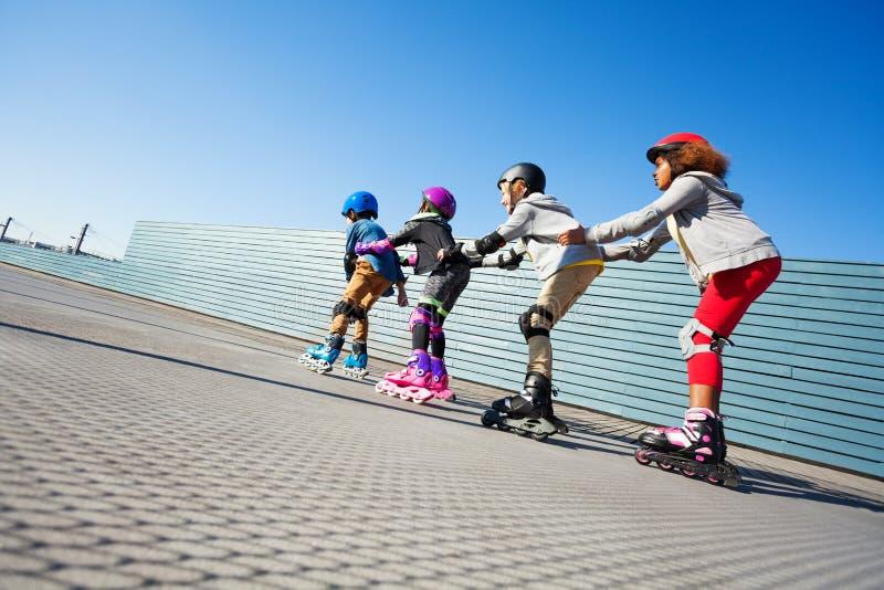 Happy preteen kids having fun while rollerblading stock image