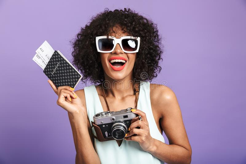 Happy pretty african woman in sunglasses praparing to trip. And rejoices while looking at the camera over violet background stock photography