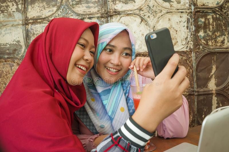 Happy and pretty Asian Indonesian girls in traditional Islamic hijab head scarf taking selfie together having fun at cafe in stock image