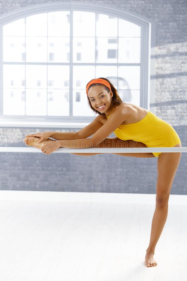 Happy pretty ballerina stretching. At ballet training room, standing at bar royalty free stock photo