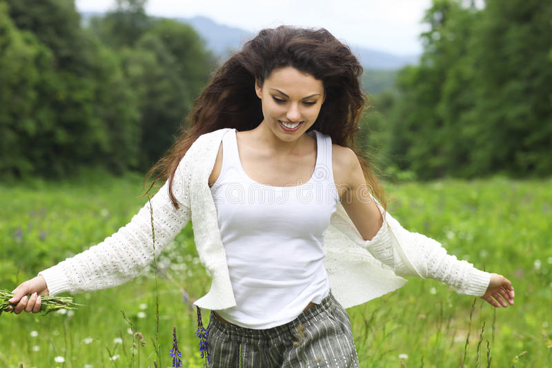 Happy pretty brunette woman in chamomile field, cute female relaxed on flowers meadow stock photography
