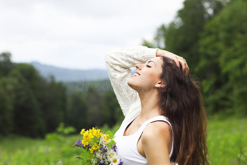 Happy pretty brunette woman in chamomile field royalty free stock photo
