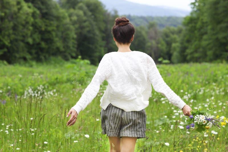 Happy pretty brunette woman in chamomile field royalty free stock photo