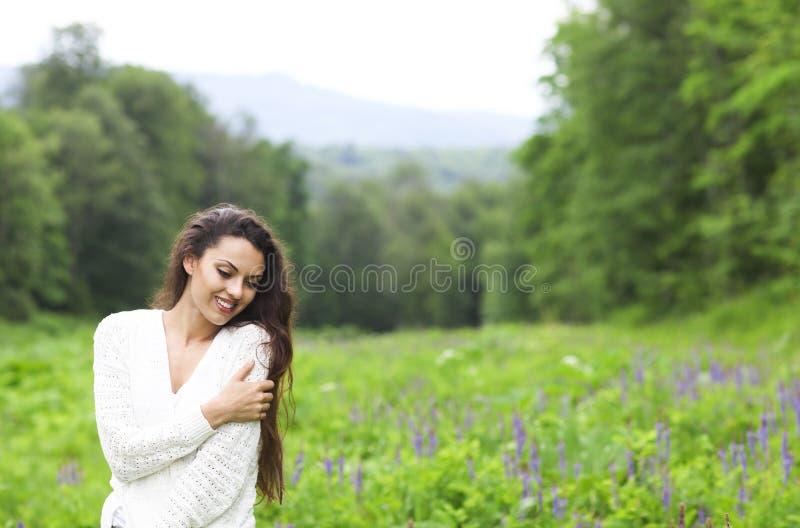 Happy pretty brunette woman in flower field royalty free stock photography