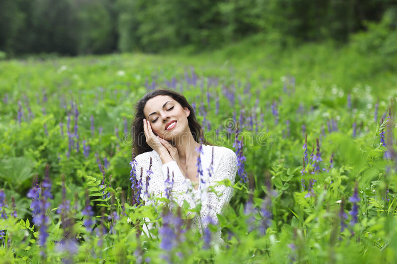 Happy pretty brunette woman in flower field stock photo
