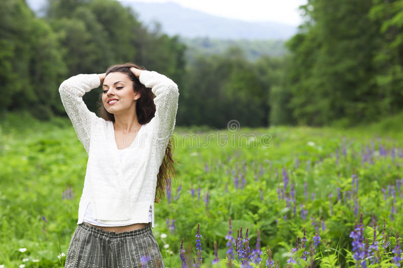 Happy pretty brunette woman in flower field royalty free stock photography