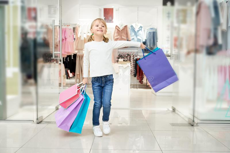 Happy girl posing in shopping centre with many bags. royalty free stock photo