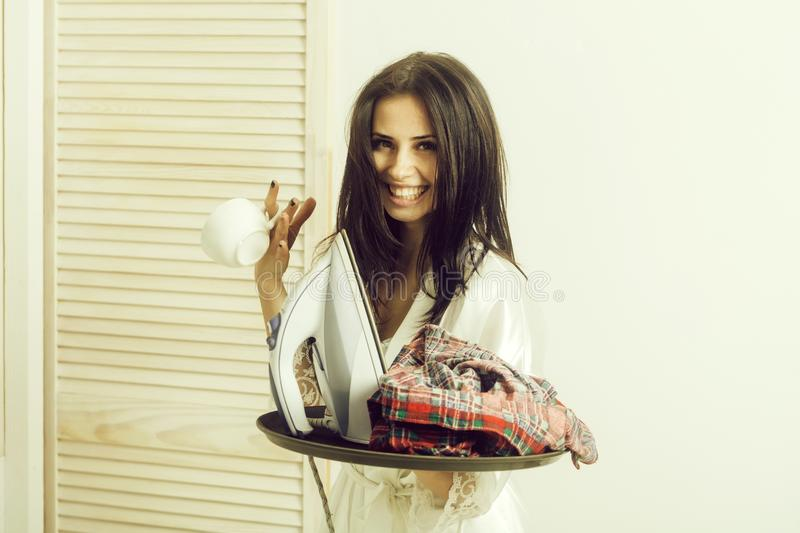 Happy pretty housewife with iron and clothes on tray. Happy pretty girl or beautiful woman, housewife, with long brunette hair in sexy dressing gown smiling with royalty free stock image