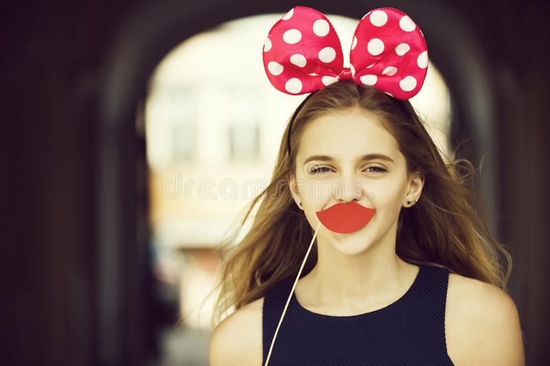 Happy pretty girl with cute mouse ears and red lips. Fun party. Happy pretty girl or young woman, teenager, with long, blond hair posing with cute mouse ears and stock photo