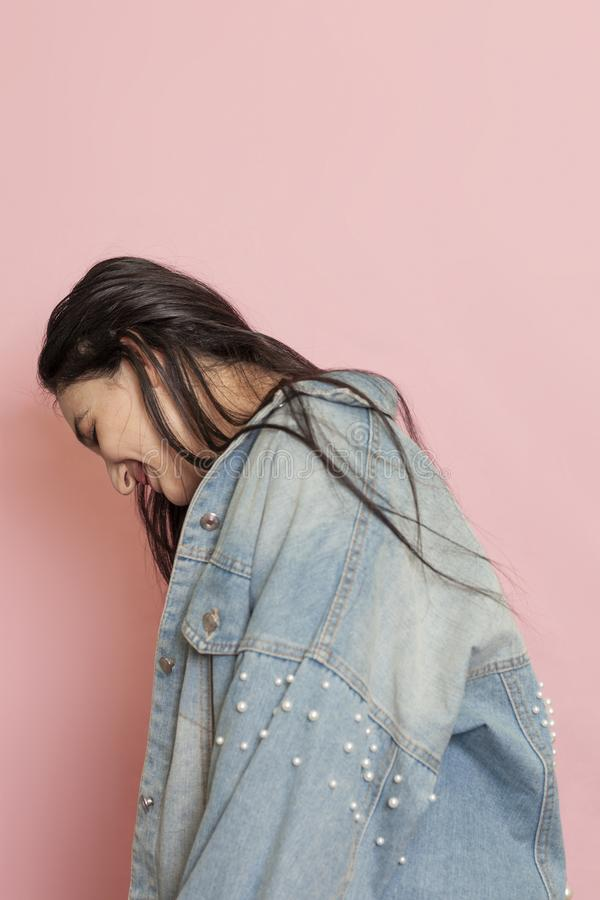 Happy pretty girl in denim jacket laughing. Emotional portrait of a young and stylish woman with long hairs stock images