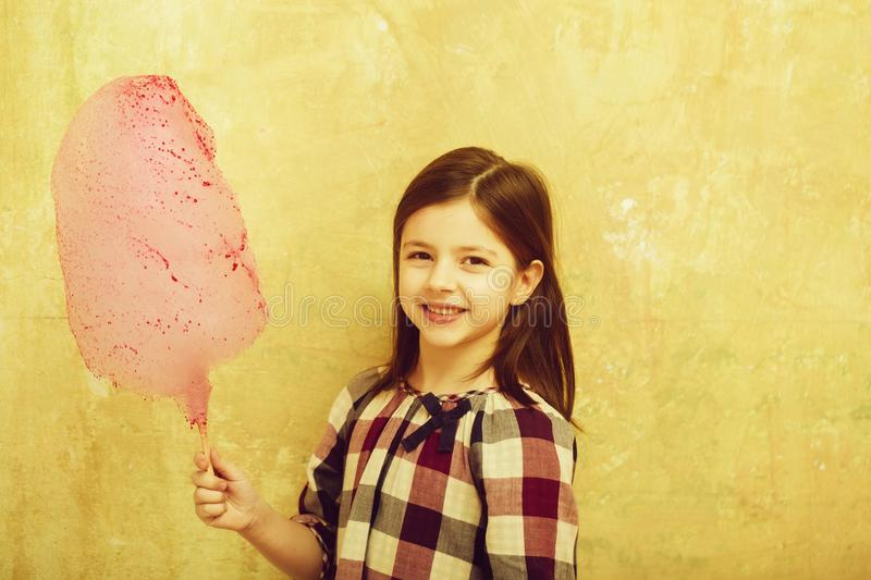 Happy pretty girl smiling with cotton candy on stick. Happy, pretty girl, small, little, child in plaid dress smiling with tasty, pink, cotton candy, sweet stock photos