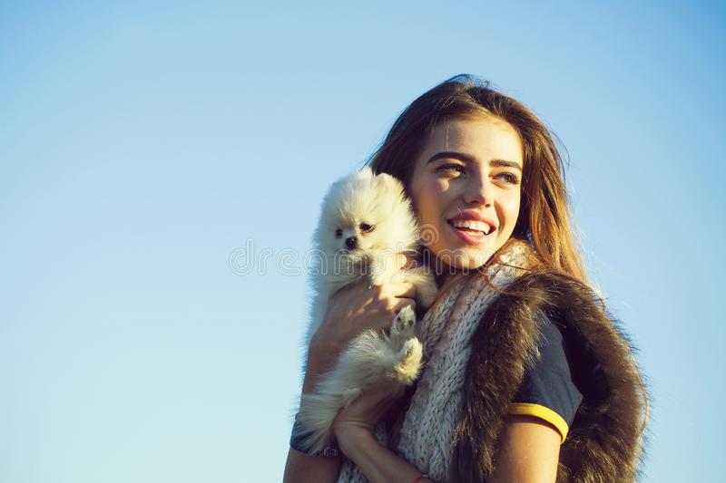 Happy girl keeps cute dog. Happy pretty girl smiling young beautiful woman in fur vest keeps cute small dog pet in hands outdoors on blue sky stock photos