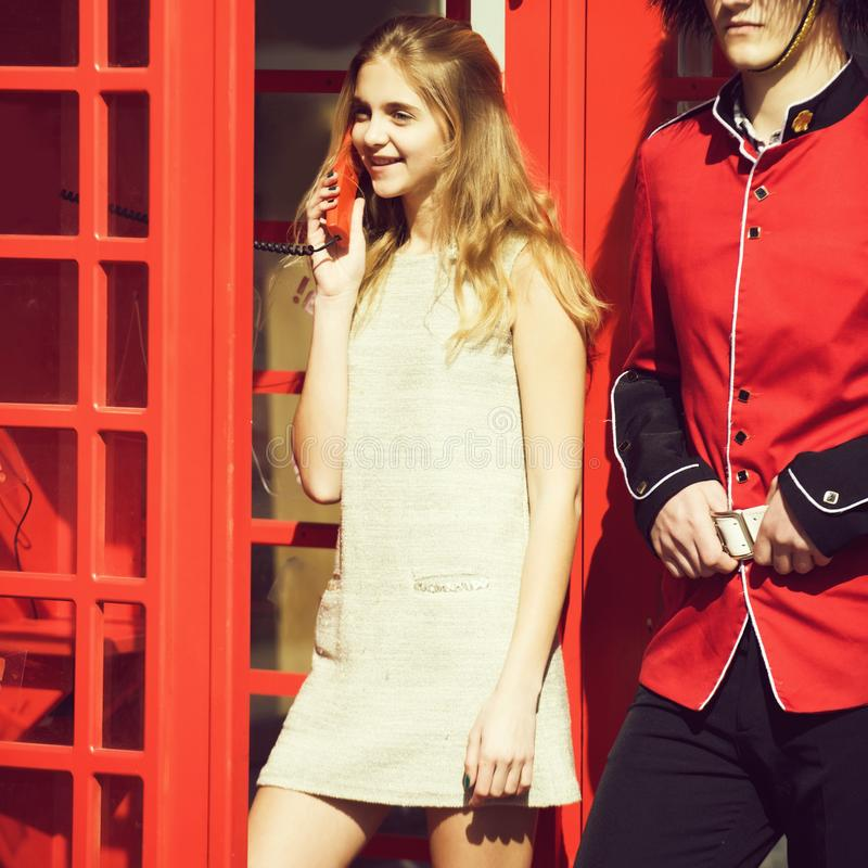 Happy pretty girl talking on phone in red telephone box royalty free stock photo