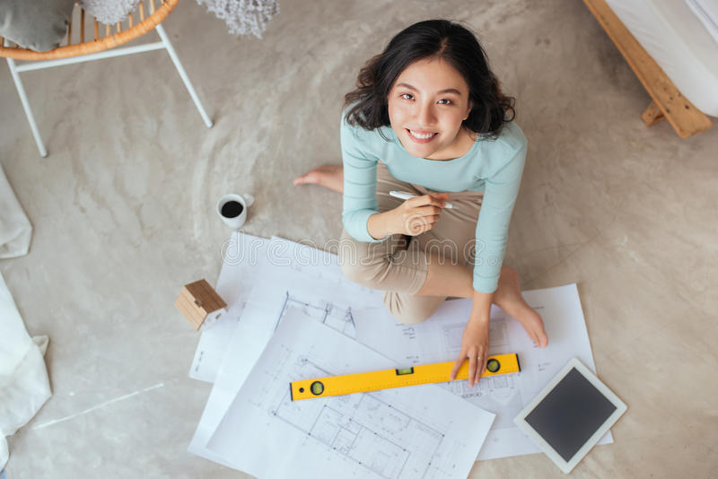 Happy pretty housewife holding new house interior sketch paper royalty free stock photos
