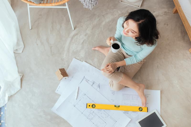 Happy pretty housewife holding new house interior sketch paper royalty free stock image