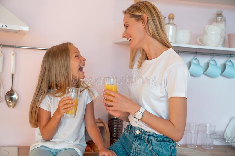 Happy pretty mom and her little daughter are drinking orange juice in the kitchen looking at each other and laughing . Happy stock photo