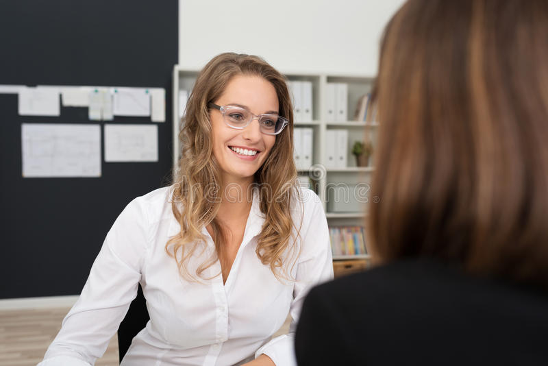 Happy Pretty Office Woman Talking to Office-mate royalty free stock photography