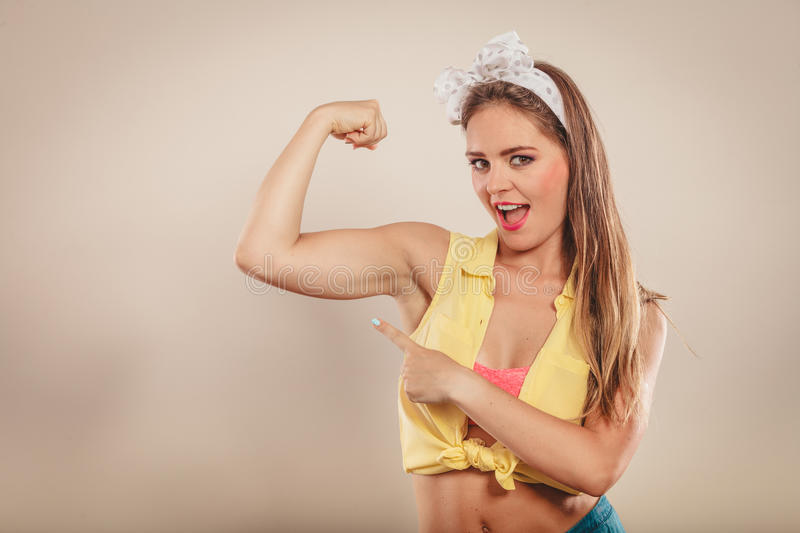 Happy pretty pin up girl showing off muscles. royalty free stock photo