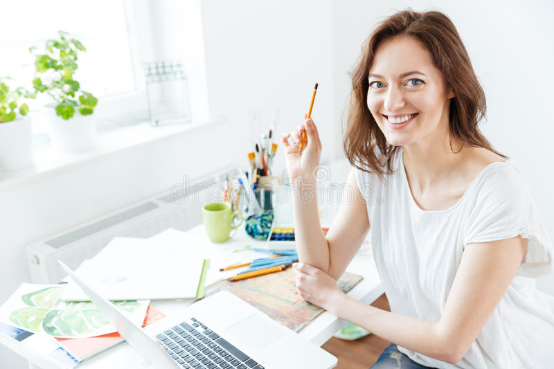 Happy pretty woman artist using laptop in art studio stock images