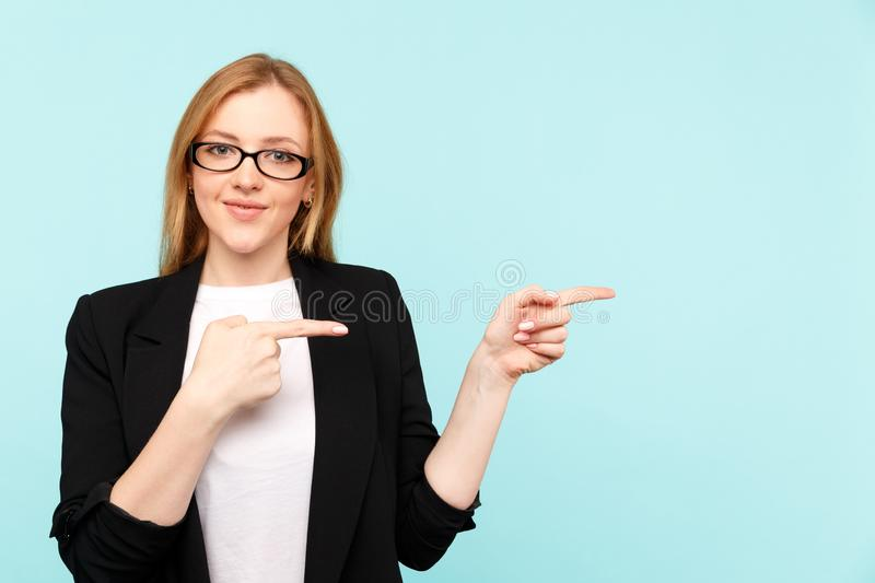 Happy pretty woman in glasses pointing something in the blue studio. royalty free stock photography