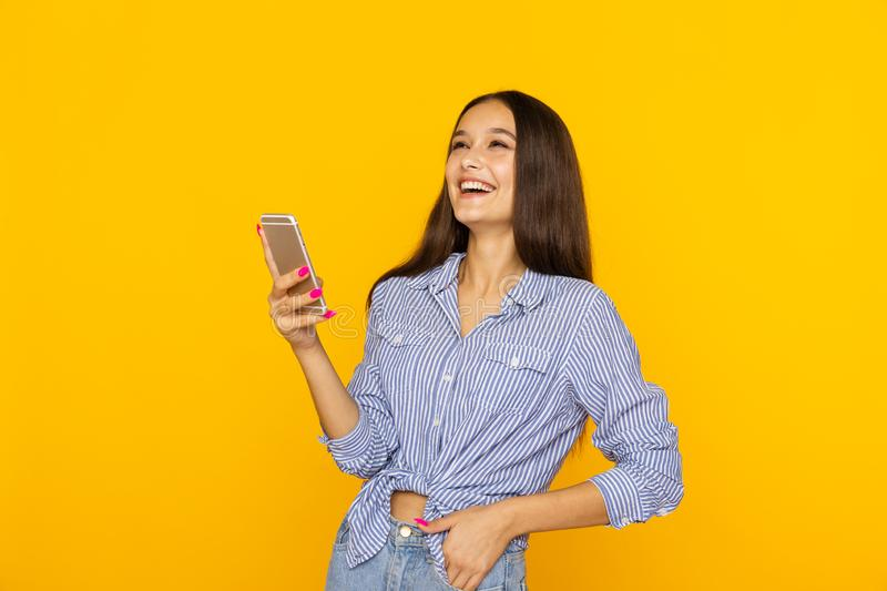 Happy pretty woman with phone lauthing in the yellow studio. royalty free stock photo