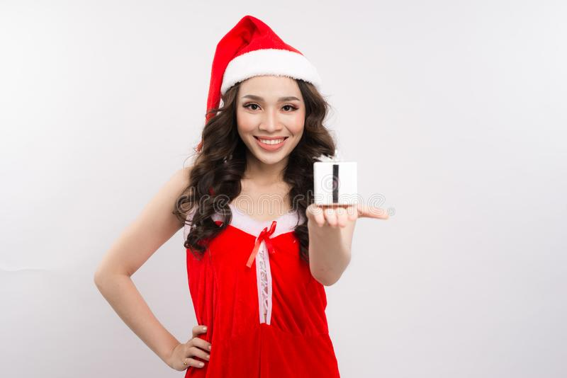 Happy pretty woman in red dress and santa claus hat holding gift stock photos