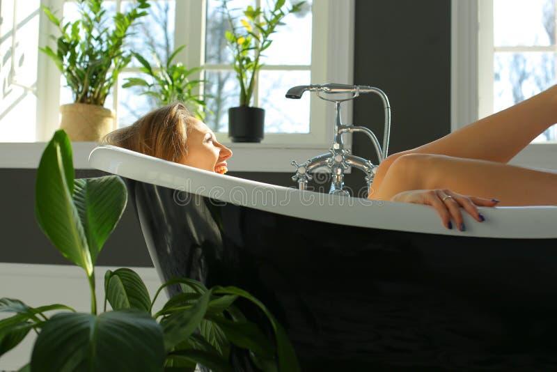 Happy pretty woman is relaxing in bath stock photo