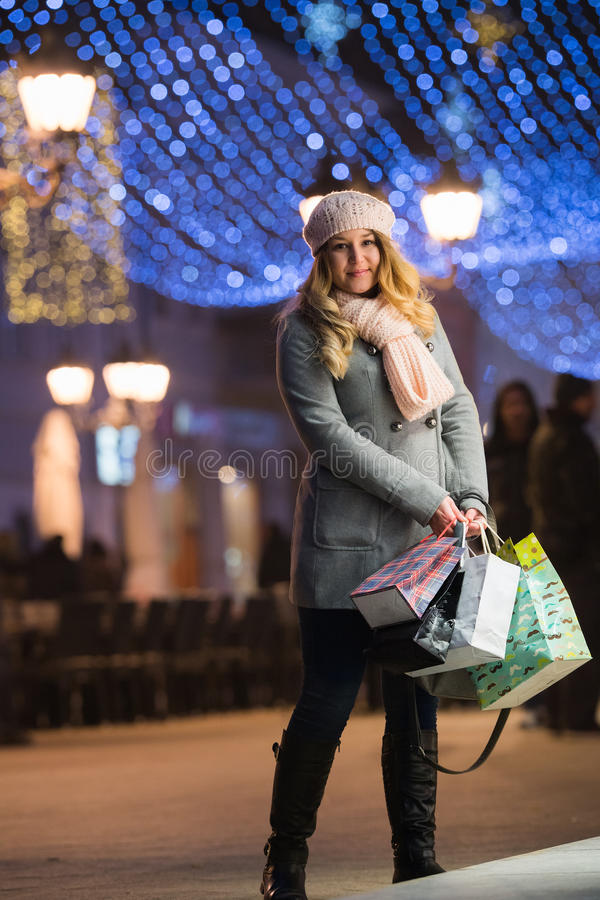 Happy pretty woman walking at night with christmas decorations. Young happy pretty woman walking at night with christmas decorations royalty free stock images