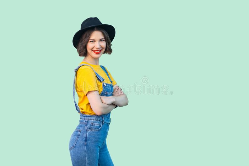 Happy pretty young hipster girl in blue denim overalls, yellow shirt and black hat standing, crossed arms and looking at camera stock images