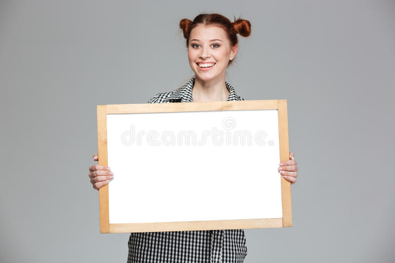 Happy pretty young woman with blank whiteboard. Over grey background stock photo