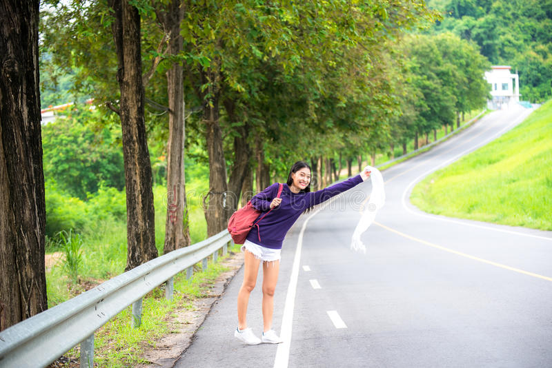 Happy pretty young woman with hand up calling passing car. On countryside street stock photo