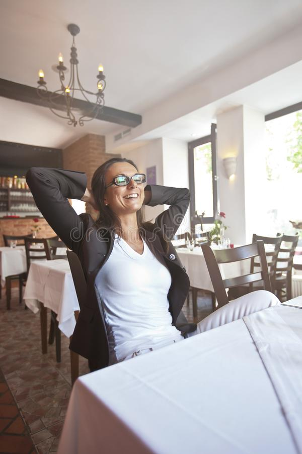 Happy and pretty young woman sitting in a restaurat stock photo