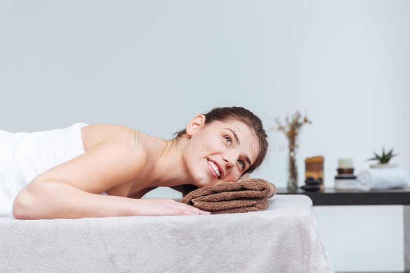 Happy pretty young woman smiling and lying in spa salon stock photos